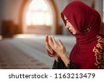 young muslim woman praying in...   Shutterstock . vector #1163213479