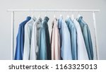 assorted blue shirts hanging on ...   Shutterstock . vector #1163325013