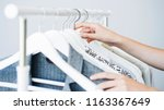woman choosing clothes on a rack | Shutterstock . vector #1163367649