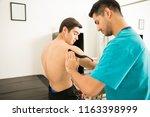 male therapist applying elastic ... | Shutterstock . vector #1163398999