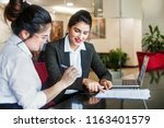 Small photo of Indian female agent helping client sign the application document