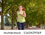fit middle aged woman jogging...   Shutterstock . vector #1163429569