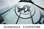 two skydivers fly into wind... | Shutterstock . vector #1163435386
