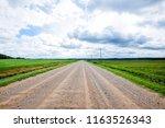a dirt road through the green... | Shutterstock . vector #1163526343