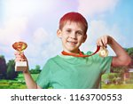 boy sportsman winner with cup... | Shutterstock . vector #1163700553