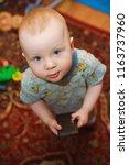 little boy stands  keeps his... | Shutterstock . vector #1163737960