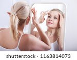 middle aged woman looking at... | Shutterstock . vector #1163814073