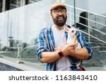 Stock photo weekend walk dark haired man laughing out loud while enjoying weekend walk with little white dog 1163843410