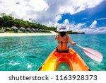 woman in white hat kayaking in... | Shutterstock . vector #1163928373