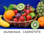 many fruits in a basket on blue ... | Shutterstock . vector #1164027373