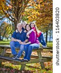 family sitting on bench during... | Shutterstock . vector #116403820