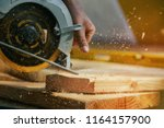 Circular Saw. Carpenter Using Circular Saw for wood beam - stock photo