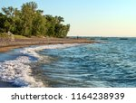 Deserted beach with lifeguard chairs and trees in background on Presque Isle on Lake Erie