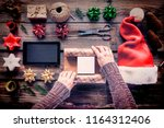christmas. woman is packaging... | Shutterstock . vector #1164312406