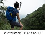 woman hiking in forest taking a ... | Shutterstock . vector #1164512713