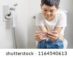 asian boy sitting on toilet... | Shutterstock . vector #1164540613