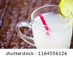 glass of lemon juice on blur... | Shutterstock . vector #1164556126