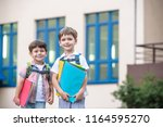 Small photo of Cute little school students briskly talk on the schoolyard. Children have a good mood. Warm spring morning. Behind shoulders at schoolmates schoolbags. In hands of one of boys bright red folder.