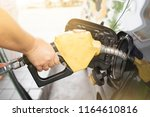 a woman pumping gasoline with a ... | Shutterstock . vector #1164610816
