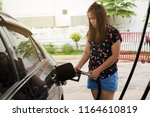 a woman pumping gasoline with a ... | Shutterstock . vector #1164610819