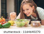 smiling young woman cooking in... | Shutterstock . vector #1164640270