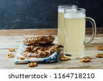 Rustic background for Oktoberfest or Bavarian specialties with white and blue fabric, beer glass and pretzels on wooden table. Menu card for Restaurants. vintage toned