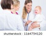 dedicated female physician... | Shutterstock . vector #1164754120