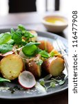 Fresh healthy potato salad with peas, green shoots, radish and mustard dressing. styled by food stylist - stock photo