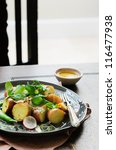 Gourmet potato salad with greens served on wooden table as light meal, lunch or dinner - stock photo