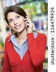 Young woman smiling and speaking on phone during shopping at supermarket store - stock photo