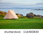 Camping tent on a shore in a morning light - stock photo