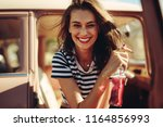 young woman sitting in the car... | Shutterstock . vector #1164856993