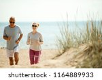 cheerful and active couple of... | Shutterstock . vector #1164889933