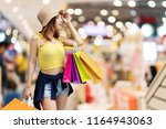 cheerful young woman holding... | Shutterstock . vector #1164943063