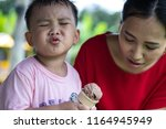 Small photo of funny face of little child with ice cream melting on lips holding ice cream cone in hand with mother in red t-shirt looking after beside