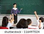 teacher standing by blackboard