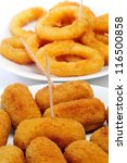 closeup of some plates with spanish croquettes and calamares a la romana, breaded and fried rings of squid, on a white background - stock photo