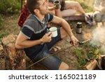 cheerful hunter sitting near... | Shutterstock . vector #1165021189