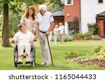 an elderly disabled couple with ... | Shutterstock . vector #1165044433
