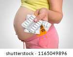 pregnant woman with pills in... | Shutterstock . vector #1165049896