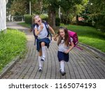 two happy schoolgirls hold... | Shutterstock . vector #1165074193