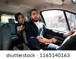 taxi driver driving a car and... | Shutterstock . vector #1165140163