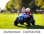 kids driving electric toy car... | Shutterstock . vector #1165161436