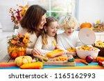 mother and kids cutting pumpkin ... | Shutterstock . vector #1165162993