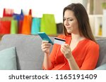 confused woman paying online... | Shutterstock . vector #1165191409