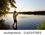 angler standing in a lake and... | Shutterstock . vector #1165197853