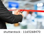 businessman cutting red ribbon... | Shutterstock . vector #1165268470