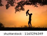 happy father lifting son in the ... | Shutterstock . vector #1165296349