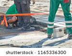 a workman's gloved hands use a... | Shutterstock . vector #1165336300