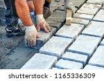 a workman's gloved hands use a... | Shutterstock . vector #1165336309